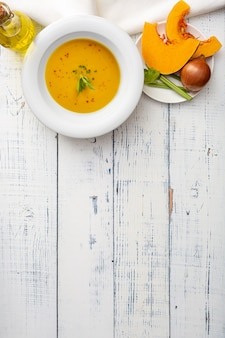Soupe à la citrouille dans une assiette en céramique blanche sur une table en bois.