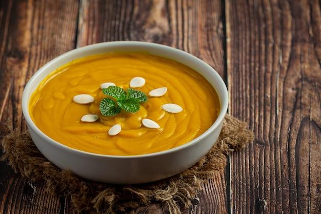 Soupe à la citrouille dans un bol blanc placé sur un plancher en bois