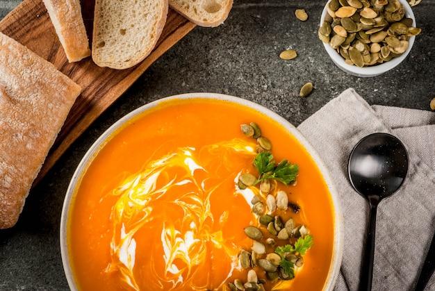Soupe de citrouille épicée avec des graines de citrouille, de la crème et de la baguette fraîchement cuite sur une table en pierre noire