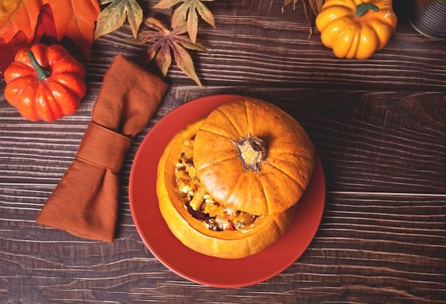 Soupe de citrouille fraîchement cuite servie dans une citrouille. cuisine d'automne chaleureuse et confortable.