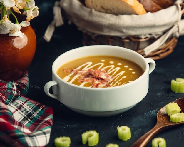 Soupe de citrouille avec des morceaux de poulet grillés garnis de tranches de bâton de cellier