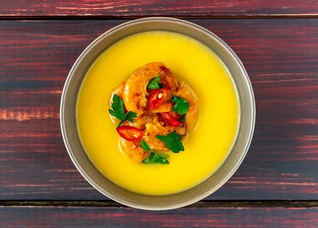 Soupe de crème au fromage aux crevettes grillées sur un fond en bois.