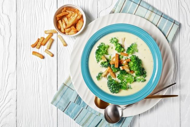 Soupe à la crème avec brocoli et croûtons dans un bol bleu sur une table en bois blanc avec cuillères et serviette, vue horizontale d'en haut, mise à plat, espace libre
