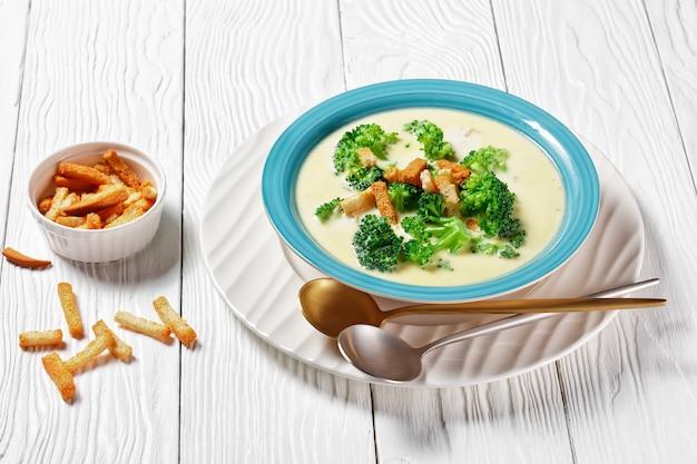 Soupe à la crème avec brocoli et croûtons dans un bol bleu sur une table en bois blanc avec cuillères , vue horizontale d'en haut