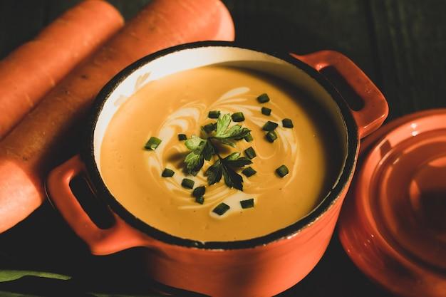 Soupe à la crème de carottes sur une casserole en bois vert foncé avec couvercle orange avec deux carottes fraîches et ciboulette