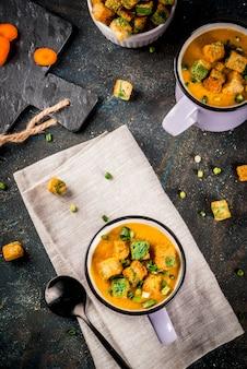 Soupe à la crème de carottes en purée maison, avec des craquelins de pain, des herbes fraîches et de la crème