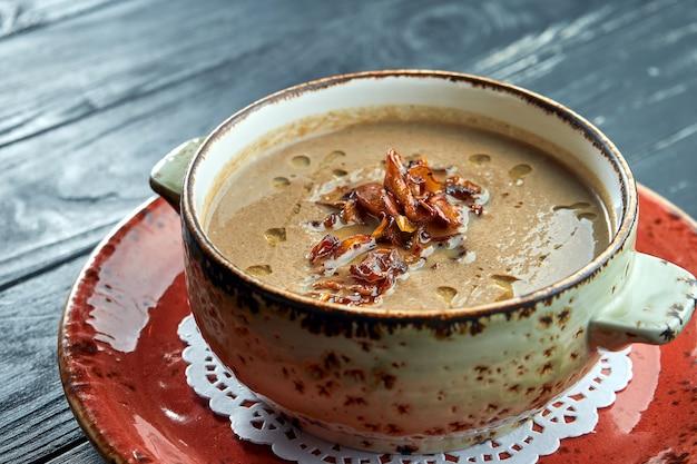 Soupe à la crème de champignons appétissante avec de l'huile d'olive et des champignons frits, servie dans un bol sur une surface noire. alimentation diététique