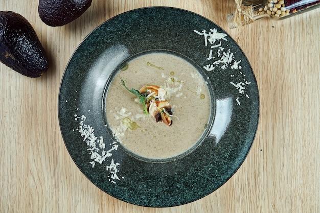 Soupe à la crème de champignons et champignons, garnie de champignons frits, d'huile d'olive et de parmesan râpé dans un bol gris sur une table en bois. régime équilibré. nourriture vue de dessus