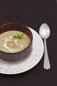 Soupe à la crème de champignons avec de la crème servie dans un bol au-dessus de la vue de dessus verticale