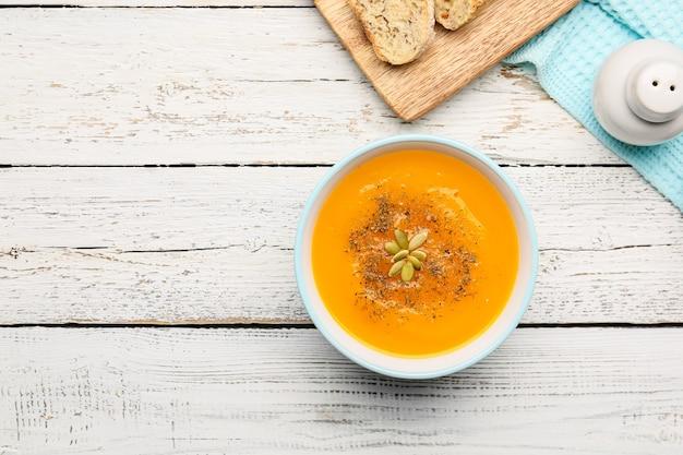 Soupe à la crème de citrouille savoureuse dans un bol sur la table
