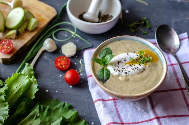 Soupe à la crème de courgettes saine servie avec œuf poché et légumes verts. une bonne alimentation nutritionnelle