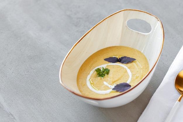 Soupe à la crème de légumes dans un bol sur une table grise