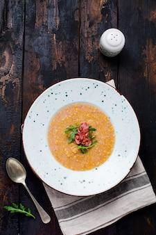 Soupe à La Crème De Lentilles Rouges Maison Avec Bacon Et Roquette Dans Une Assiette Blanche Sur Une Vieille Surface En Bois. Style Rustique. Vue De Dessus. Photo Premium