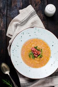 Soupe à la crème de lentilles rouges maison avec bacon et roquette dans une assiette blanche sur une vieille table en bois