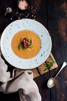 Soupe à la crème de lentilles rouges maison avec bacon et roquette dans une assiette blanche sur un vieux fond en bois