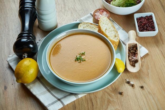 Soupe à la crème de lentilles avec une tranche de citron sur un plateau en bois dans un bol bleu. nourriture saine et végétalienne. mettre au vert. fermer