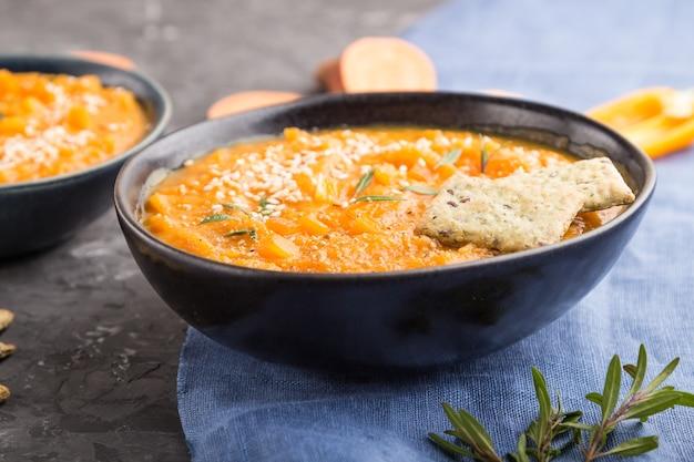 Soupe à la crème de patate douce ou batata aux graines de sésame et des collations dans des bols en céramique bleue sur une surface en béton noir avec textile en lin bleu