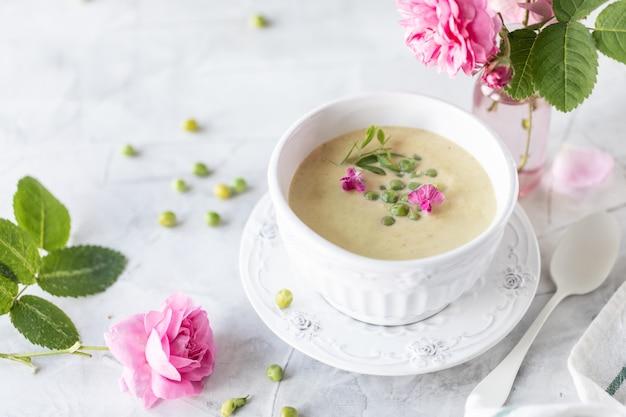 Soupe à la crème de pois verts sur fond de marbre blanc avec un bouquet de roses