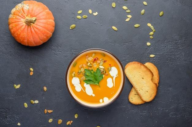 Soupe à la crème de potiron d'automne maison avec de la crème, des croûtons, des graines et du basilic sur un fond en bois foncé.