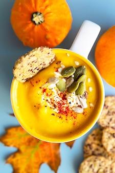 Soupe à la crème de potiron avec des graines et de la crème dans une tasse en céramique et des craquelins sains multigrains.