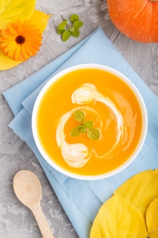 Soupe à la crème de potiron traditionnelle dans un bol blanc sur une surface en béton gris avec une serviette bleue. vue de dessus, gros plan.