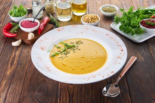 Soupe à la crème de potiron végétalien biologique sur table en bois avec des ingrédients, concept d'alimentation saine