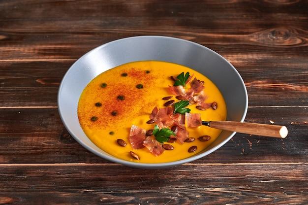 Soupe à la crème de purée de citrouille traditionnelle avec carottes oignons gingembre ail lait de coco graines ajoutées