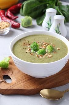 Soupe à la crème végétarienne avec brocoli, épinards et courgettes dans un bol blanc sur fond gris. fermer. format vertical