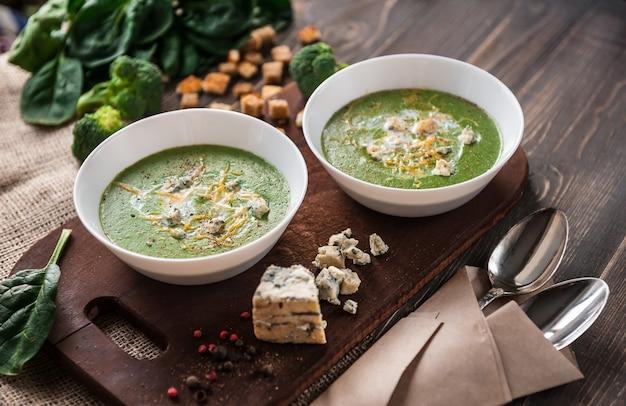 Soupe à la crème verte d'épinards et de brocoli. avec l'ajout de parmesan et de fromage bleu avec des croûtons. une surface en bois.