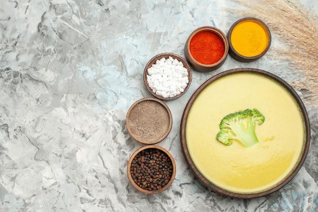 Soupe crémeuse au brocoli dans un bol brun et différentes épices sur table grise