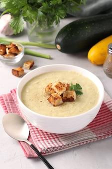 Soupe crémeuse au poulet et aux courgettes servie avec des croûtons de pain blanc dans un bol blanc sur une surface grise. format vertical