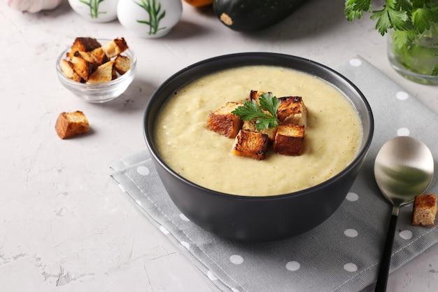 Soupe crémeuse au poulet et aux courgettes, servie avec des croûtons de pain blanc dans un bol sombre sur fond gris. fermer