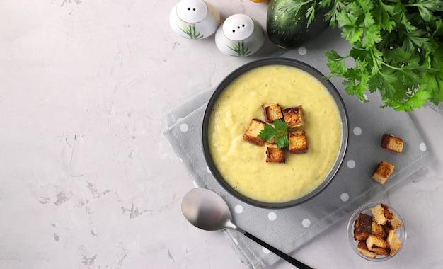 Soupe crémeuse au poulet et aux courgettes servie avec des croûtons de pain blanc dans un bol sombre sur une surface grise. espace pour le texte