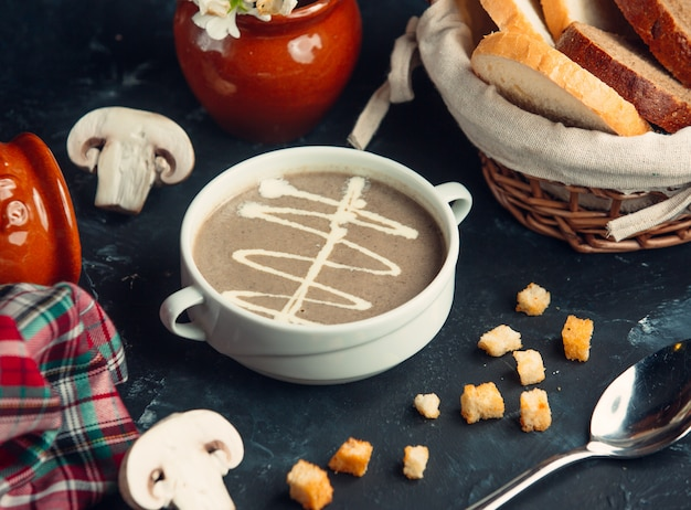 Soupe crémeuse aux champignons servie avec du pain