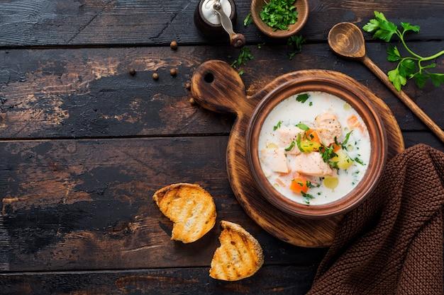 Soupe crémeuse finlandaise chaude avec du saumon et des légumes dans un vieux bol en céramique sur fond de bois ancien. style rustique. vue de dessus.