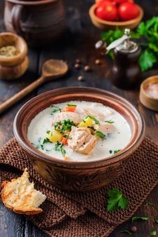 Soupe crémeuse finlandaise chaude avec du saumon et des légumes dans un vieux bol en céramique sur fond de bois ancien.