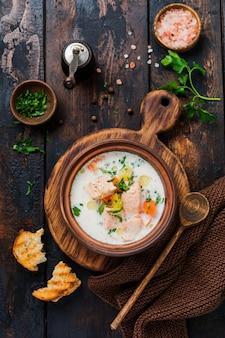 Soupe crémeuse finlandaise chaude avec du saumon et des légumes dans un vieux bol en céramique sur une vieille surface en bois. style rustique. vue de dessus.