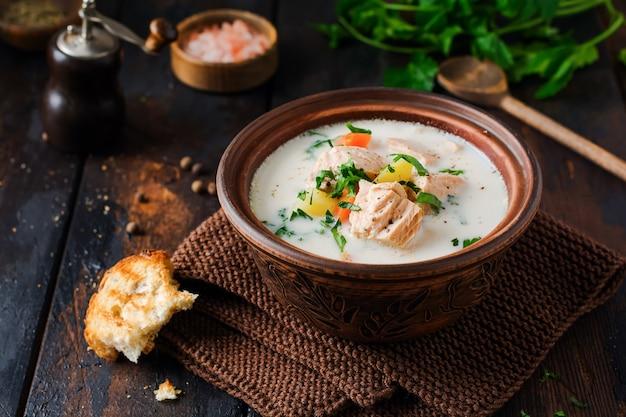 Soupe crémeuse finlandaise tiède au saumon et légumes dans un vieux bol en céramique sur la vieille table en bois