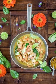 Soupe de crevettes au curry servi dans un pot en argent sur une table brune