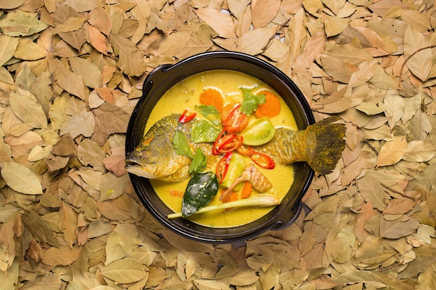 Soupe de curry de poisson blanc snapper avec tomate, piment rouge et feuille de lime