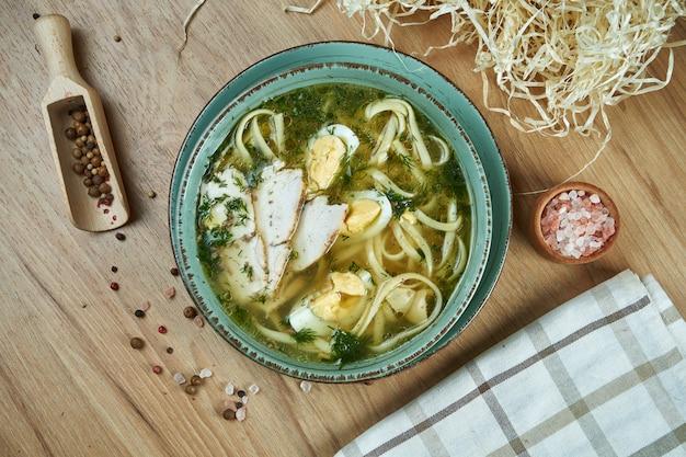 Soupe diététique au poulet, légumes et persil en compostion avec des ingrédients sur une table en bois dans un bol en céramique bleu. vue de dessus soupe savoureuse. nourriture plate