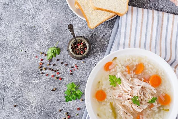 Soupe diététique au poulet avec riz et carottes. nourriture saine. mise à plat. vue de dessus