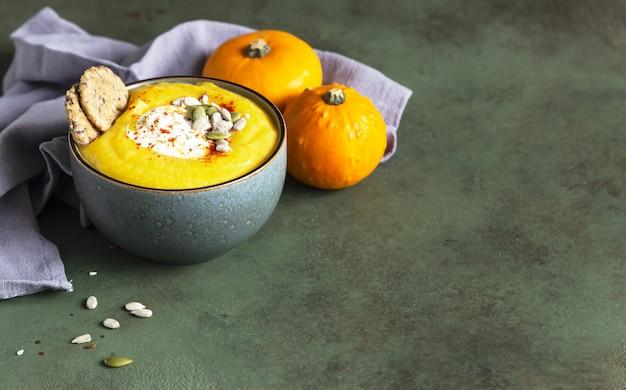 Soupe épaisse à la citrouille avec des craquelins multigrains à la crème et des graines dans un bol nourriture végétarienne saine