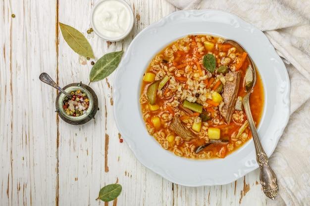 Soupe épaisse et consistante avec du bœuf, des légumes (cornichons, carottes, oignons, pommes de terre, tomates) et de l'orge perlé