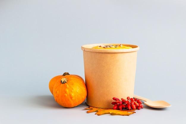 Soupe épaisse à la crème de potiron vegan avec des graines dans un gobelet jetable. soupe à emporter, livraison de nourriture saine.