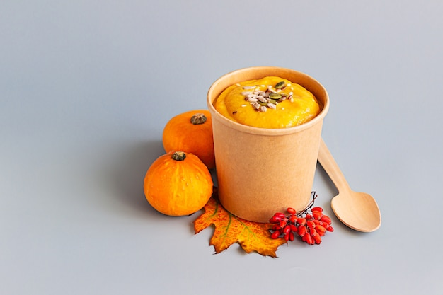 Soupe épaisse à la crème de potiron végétalienne avec des graines dans une tasse jetable de papier kraft.