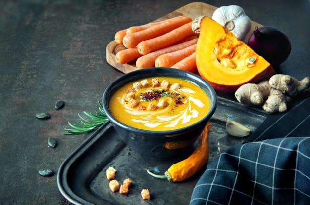 Soupe épicée à la citrouille et aux carottes avec gingembre, ail, oignon rouge et chili sur une surface sombre