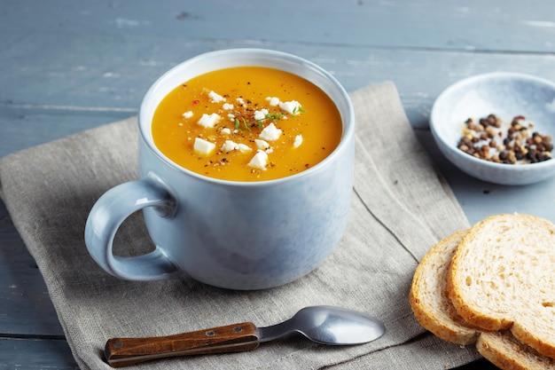 Soupe épicée à la citrouille et aux patates douces dans une grande tasse en céramique garnie de fromage feta.