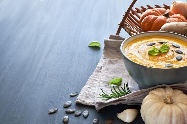 Soupe épicée à la citrouille avec carotte, piment, gingembre et ail sur fond gris, espace de texte