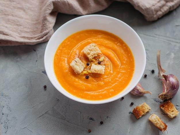 Soupe épicée à la citrouille avec croûtons et graines de citrouille.